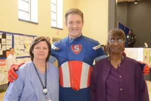 """Pictured:  Lourdes superhero, """"The Sanitizer,"""" John Groody, collaborates with Lourdes employees Patricia Spence (left), and Helen Addison (right), on best ways to fight germs and prevent infection."""